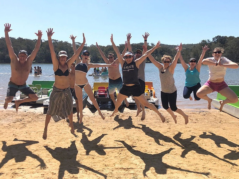Group of people jumping into the air on the beach
